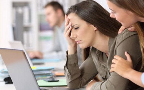 Расстроенная девушка сидит за ноутбуком, коллега пытается ее успокоить