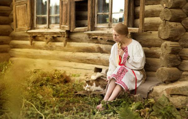 Девушка сидит возле хаты