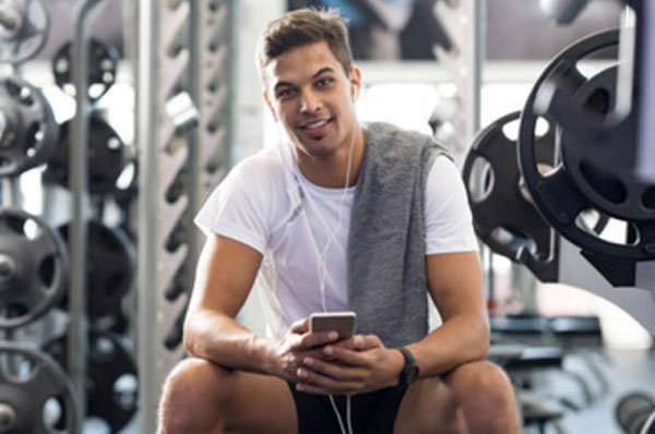 Счастливый парень с телефоном в руках сидит в тренажерном зале