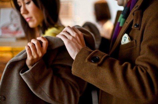 Парень помогает девушке надеть пальто