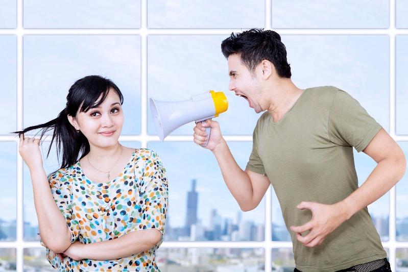Мужчина кричит на улыбающуюся женщину через рупор