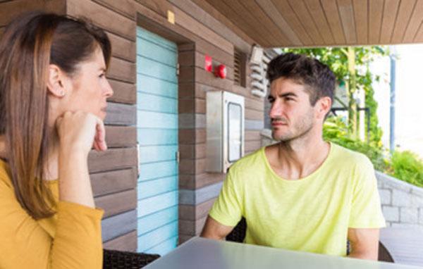 Парень разговаривает с девушкой за столом