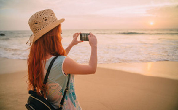 Девушка на отдыхе, фотографирует море
