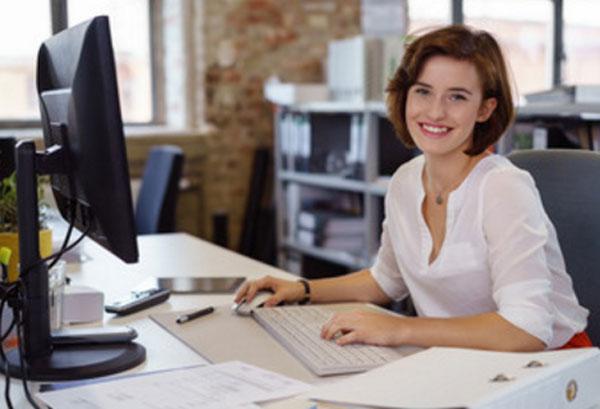 Женщина сидит за рабочим столом, перед ней компьютер, на столе бумаги, она улыбается