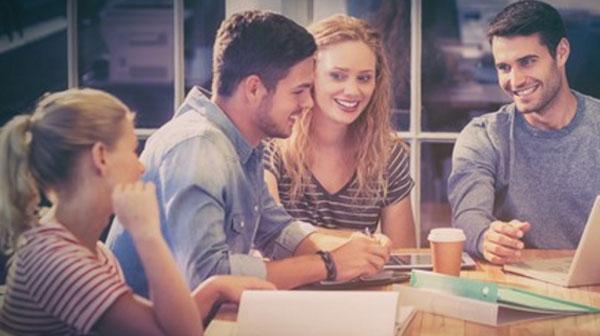 Два парня и две девушки обсуждают работу за общим столом